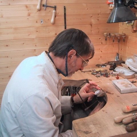Jeweller at bench making signet rings